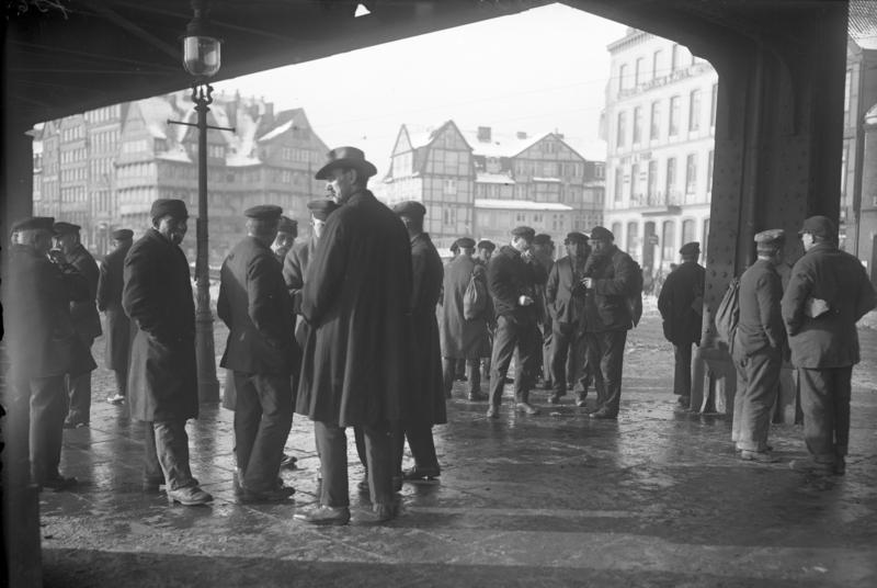 Die Not unserer Zeit! Arbeitslose Hafenarbeiter auf Abruf bei der Straßen-Arbeitsvermittlung am Baumwall, Hamburg, 1931. Von Bundesarchiv, Bild 102-11008 / CC-BY-SA 3.0