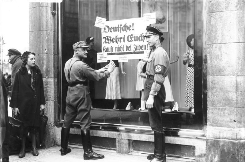 """SA - Mitglieder kleben an das Schaufenster eines Berliner jüdischen Geschäfts ein Schilder mit der Aufschrift """"Deutsche, wehrt euch, kauft nicht bei Juden"""" Bundesarchiv, Bild 102-14468 / Georg Pahl / CC-BY-SA 3.0"""