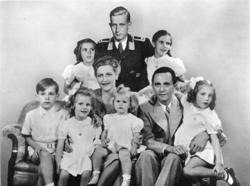 Porträt der Familie Goebbels 1942: Mitte Magda Goebbels, Joseph Goebbels mit ihren sechs Kindern Helga, Hildegard, Helmut, Hedwig, Holdine und Heidrun. Dahinter Harald Quandt in der Uniform eines Feldwebels der Luftwaffe (retuschierte Postkarte)