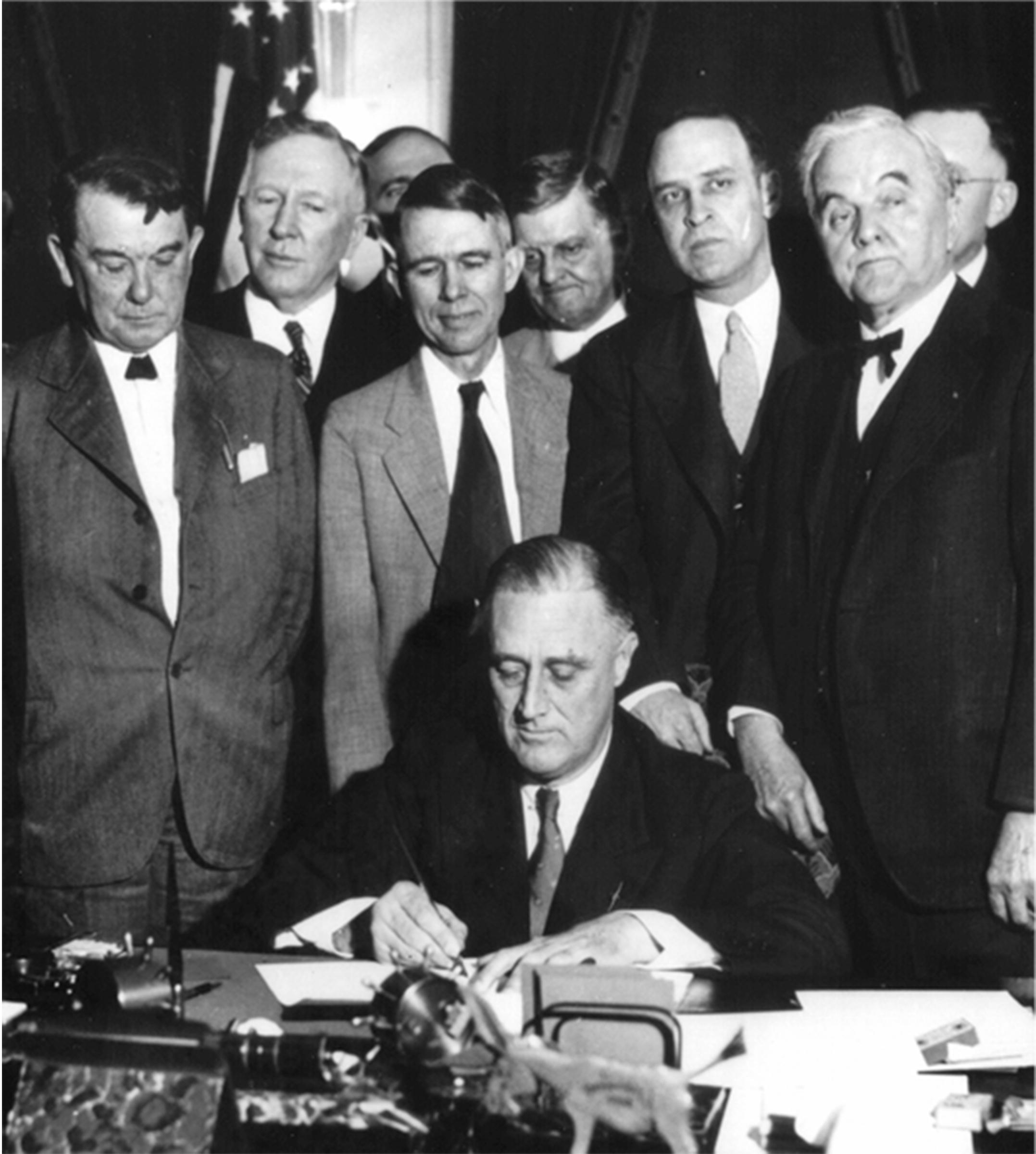 Franklin D. Roosevelt (sitzend) und George W. Norris (vorne rechts) bei der Gründung der Tennessee Valley Authority (1933)